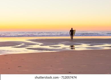 Surfer on the beach at sunrise