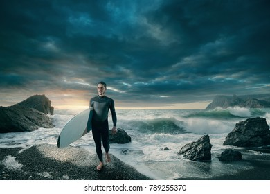 Surfer on the beach at sunset.  Young man in a wetsuit is holding a surfboard and stand near the sea with waves. Stormy ocean.