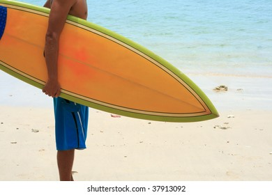 Surfer on beach with vintage retro orange surfboard