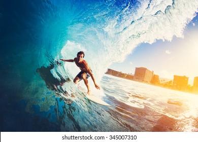 Surfer auf der Welle des blauen Ozeans Barreling bei Sonnenaufgang