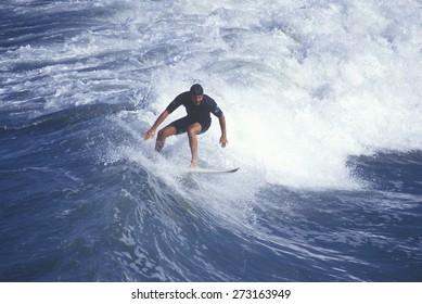 Surfer on crest of wave, Huntington Beach, CA