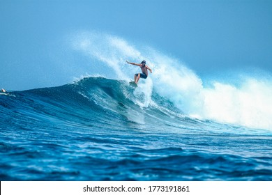 Surfer on perfect blue aquamarine wave, empty line up, perfect for surfing, clean water, Indian Ocean close to Maldivian island Himmafushi