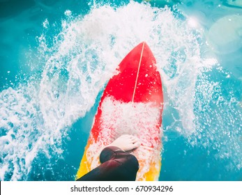 Surfer on red surfboard ride on blue wave. Surfing in ocean