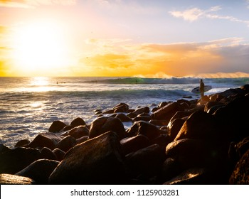 Surfer on rocks watching a surfer break through a wave loop, as the sunrises over the horizon.