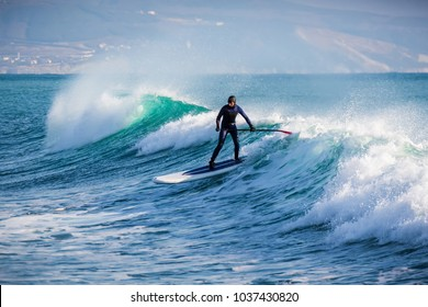Surfer on stand up paddle board ride at wave. Winter surfing in ocean