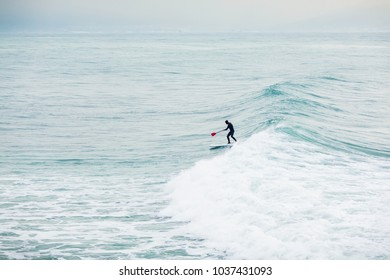 Surfer on stand up paddle board on blue wave. Winter surfing in ocean