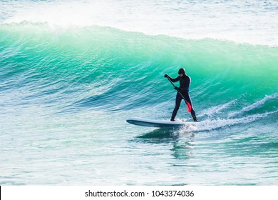 Surfer on sup board on ocean waves. Stand up paddle boarding in sea