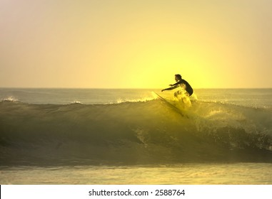 Surfer on the top of the wave with sunset