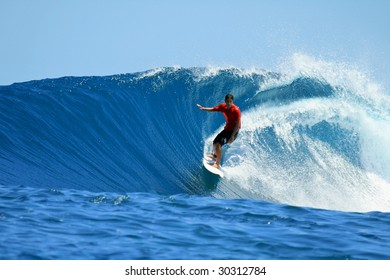 Surfer on tropical blue wave in red t-shirt, Mentawai Islands, Indonesia