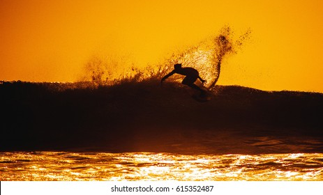 Surfer on the wave, catches a wave, surfing in the pipe. Surfing in the ocean on the island of Bali, a mellow man, a jump into the ocean. Taken from the water. Photographed from the water.
