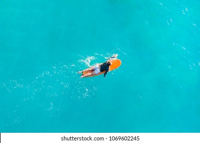 A surfer paddles on a yellow surfboard in the ocean, top view