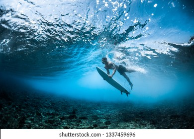 Surfer performs dive (the duck dive) with his surfboard under the wave