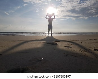 surfer posing backlight with his board
