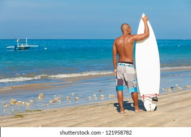 surfer posing with his surfboard