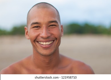 surfer posing on the beach and smiling