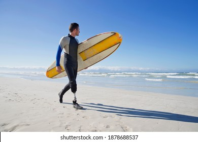 Surfer With a prosthetic Leg Walking On the Beach carrying a surf board