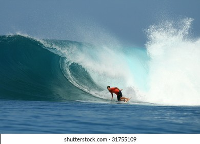 Surfer in red t-shirt on big wave, Mentawai Islands, Indonesia