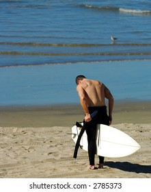 Surfer Removes Wetsuit on California Beach