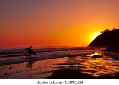 Surfer returning at Sunset, Santa Barbara, California