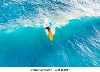 Surfer ride on the waves in the ocean, top view