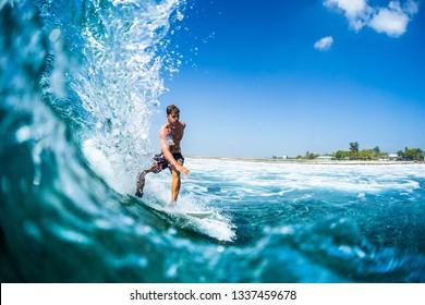 Surfer rides barreling tropical ocean wave