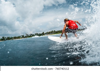 Surfer rides the ocean wave with lots of splashes. Extreme sport and outdoor activity concept