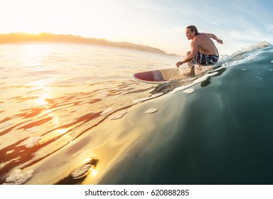 Surfer rides the perfect ocean wave at sunrise