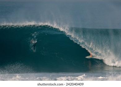 A surfer rides through a tube on an ocean wave.