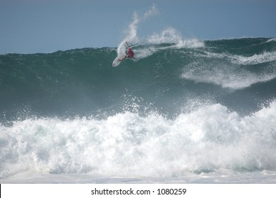 Surfer rides a wave at Bonzai Pipeline off of Oahu's North Shore. (image contains noise)