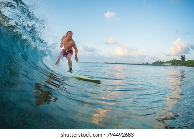 Surfer rides the wave during sunrise surf session. Maldives