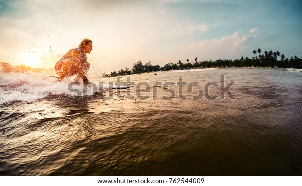 Surfer rides the wave during sunset