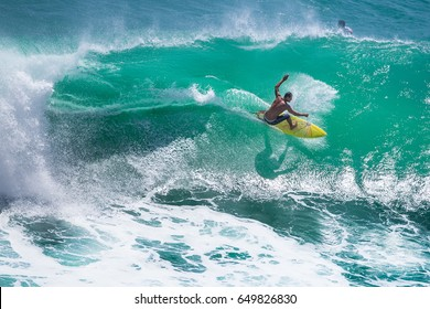 Surfer riding big wave at Padang Padang beach, Bali, Indonesia