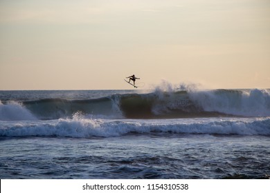 Surfer riding and jumping of the wave at Echo Beach Canggu Bali Indonesia at sunset time