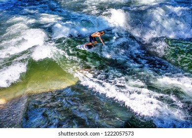 Surfer riding on wave in sea, ocean on sunny day.