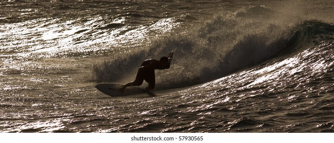 A surfer is riding a wave by sunset along beautiful Oahu, Hawaii North Shore
