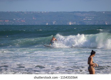 Surfer riding wave at Echo Beach Canggu Bali Indonesia. A women in the forground