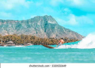 Surfer riding a wave in front of Diamond Head in Waikiki.