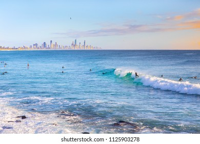 Surfer riding a wave with Surfers Paradise in the horizon at sunrise