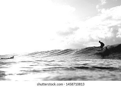 A surfer riding a wave surfs towards another surfer. Spray flies out from under his board as he glides over the glistening water. Waters are dark and the sky is white giving the image great contrast