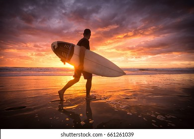 Surfer running on the beach at sunrise with reflections