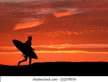 Surfer running on the cliffs at Santa Cruz, heading for the Pacific ocean as the sun sets to get in one final ride