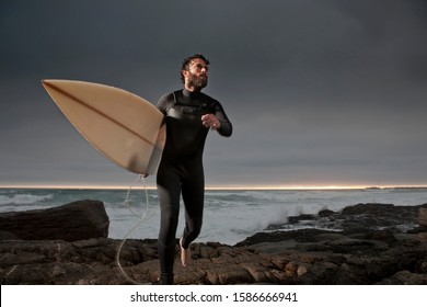Surfer running with surfboard on rocks wearing wetsuit with ocean in background and dramatic mood sky