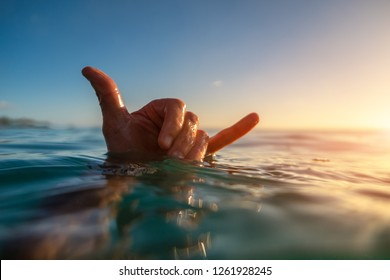 Surfer shows Hawaiian Shaka sign being in the water at sunset