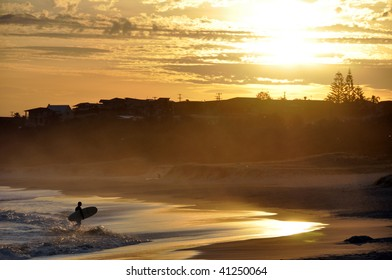 A Surfer silhouette    against a sunset backdrop