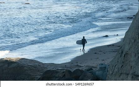 Surfer silhouette on beach at Capitola California beach around sunset.