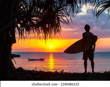 surfer silhouette  on tropical beach at sunset