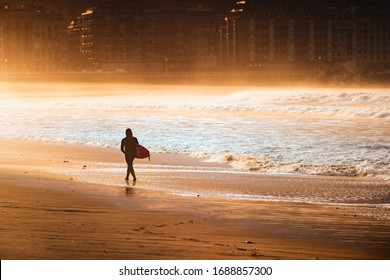 Surfer silhouette walking on an empty beach during golden hour