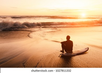 surfer sits on his board near the sea at sunset