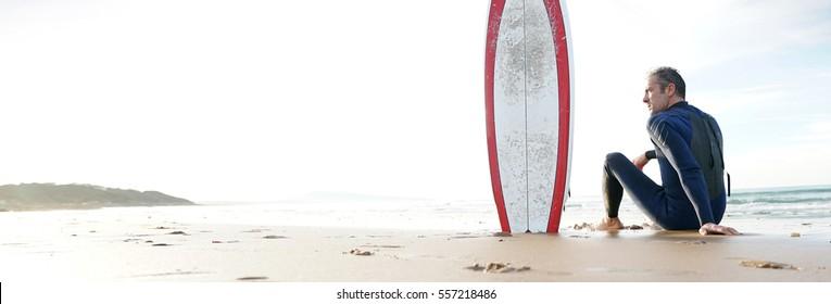 Surfer sitting on sandy beach, next to surfboard