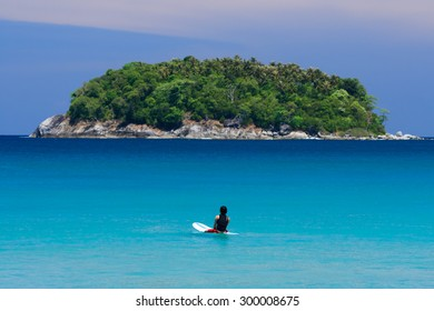 Surfer sitting on surfboard in water at the beach. Kata Beach, Phuket, Thailand.